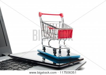 Online shopping concept - Empty Shopping Cart, laptop and tablet pc, smartphone isolated on white ba