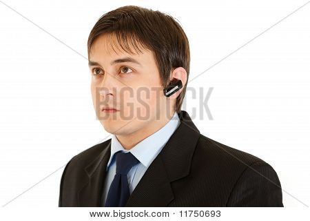 Serious modern businessman with handsfree isolated on white