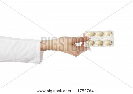 Female doctor's hand holding medical pills isolated on white background. First aid