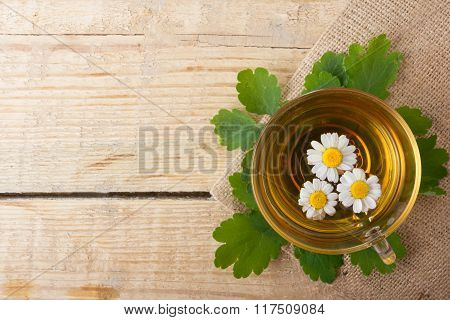 Herbal tea with chamomile on old wooden table. Top view. alternative medicine concept