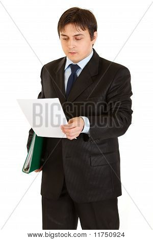 Serious modern businessman with folder in hand exploring document isolated on white