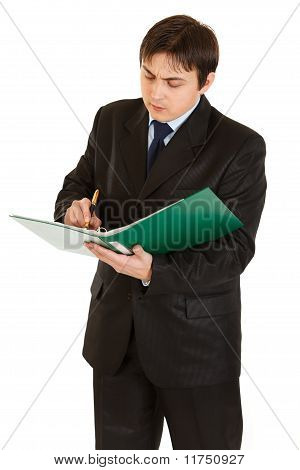 Serious young businessman holding folder in hand and making notes in document isolated on white