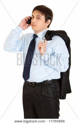 Thoughtful young businessman with jacket on his shoulder talking on mobile phone isolated on white