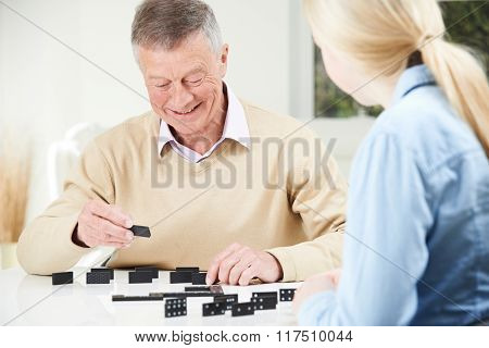 Senior Man Playing Dominoes With Teenage Granddaughter