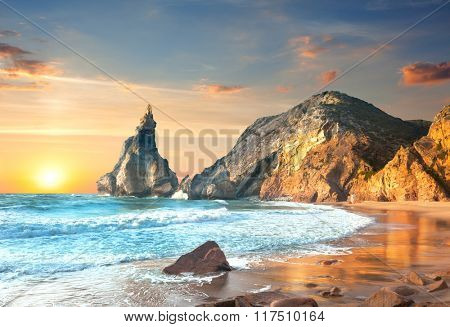 Ocean Landscape at Sundown, big rocks and stones beach. Portugal, Europe