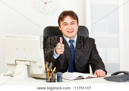 Smiling modern businessman sitting at office desk and showing thumbs up gesture