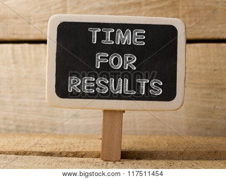 time for results concept on blackboard at wooden background.