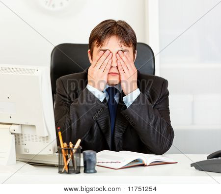 Modern businessman sitting at office desk and making see no evil gesture