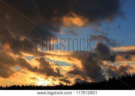 Majestic sunset sky with clouds above forest in mountains