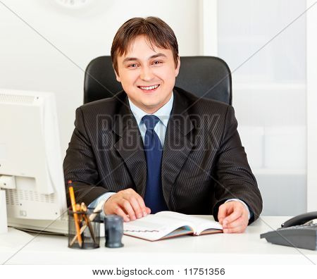Smiling modern businessman sitting at office desk