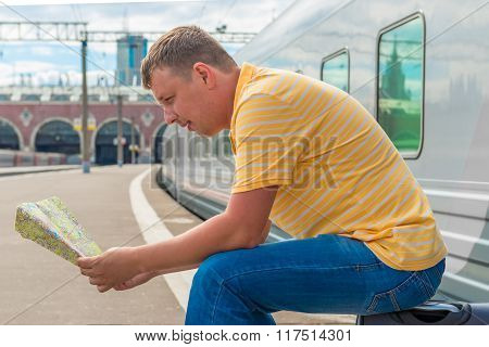 Man Sitting On A Suitcase At The Railway Station And Is Studying The Map