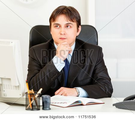 Pensive young business man sitting at desk and planning timetable in diary