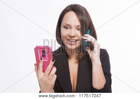 woman is looking at one phone and speaking on another