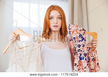 Confused cute lovely young woman choosing between two dresses standing in the room