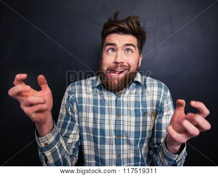 Portrait of ugly bearded young man in checkered shirt grimacing over black background