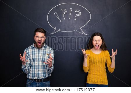 Crazy young couple standing and screaming over chalkboard background