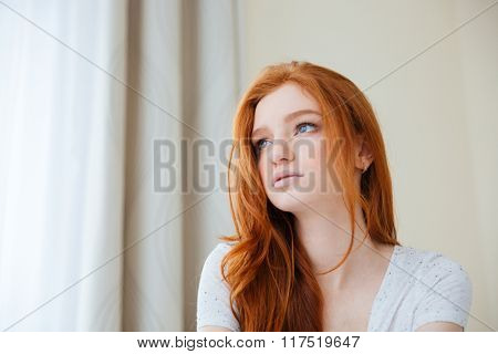 Portrait of a pensive woman looking away at home