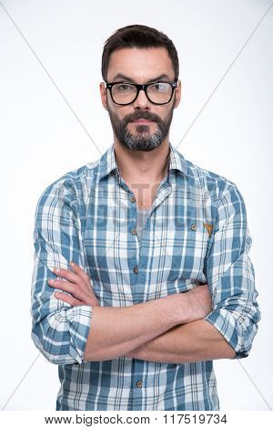 Portrait of a casual man in glasses standing with arms folded isolated on a white background and looking at camera