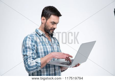 Casual man using laptop computer isolated on a white background