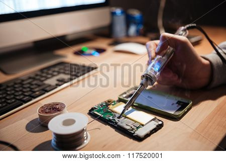 Closeup of hand of man sitting near computer and repairing cell phone with soldering iron