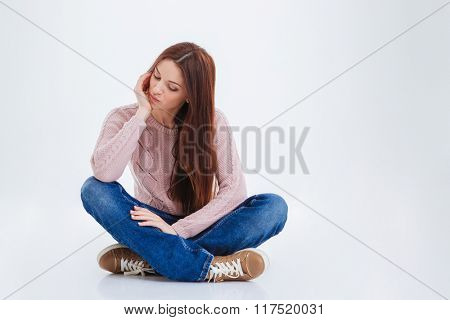 Beautiful woman sitting on the floor isolated on a white background