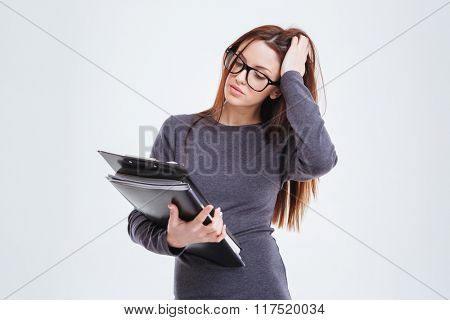 Portrait of a pensive businesswoman with folders standing isolated on a white background
