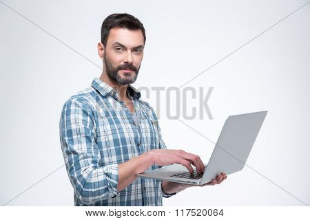 Handsome man using laptop computer and looking at camera isolated on a white background