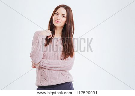 Portrait of attractive tender young woman in knitted sweater with long hair standing over white background