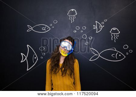 Pretty young woman in diving mask and snorkel posing over chalkboard background with drawn underwater world