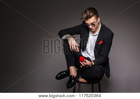 Handsome man in fashion cloth sitting on the chair and holding box with a proposal ring over black background