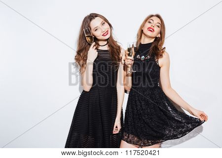 Happy two women in black dress holding glass with champagne isolated on a white background
