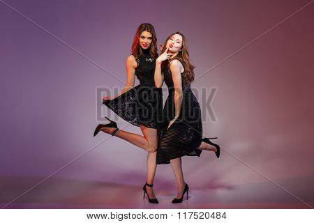 Full length portrait of a charming two women in night black dress posing over purple background
