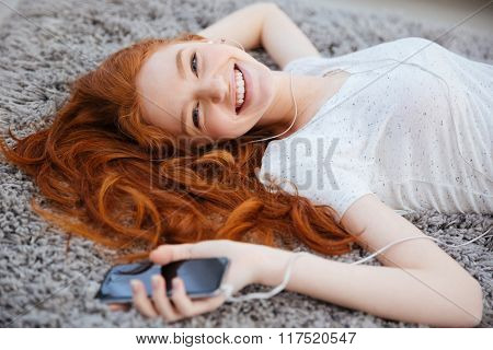 Smiling redhead woman with headphones lying on the carpet and listening music on smartphone at home