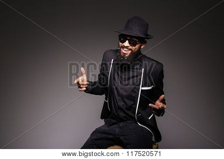 Cheerful afro american man in stylish cloth and glasses posing over black background
