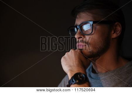 Closeup of serious focused handsome man in glasses looking at screen