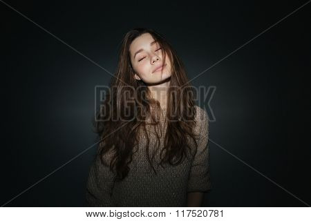 Relaxed young woman with closed eyes posing over black background