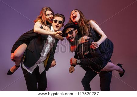 Multiethnic group of happy young people having fun over colorful background