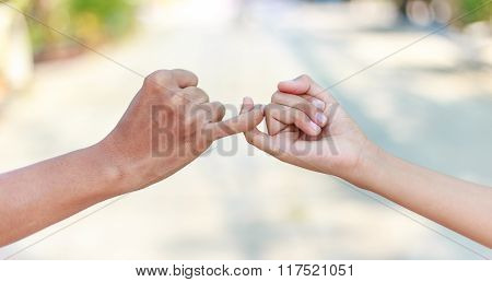 Parent And Child Hooking Their Fingers To Make A Promise