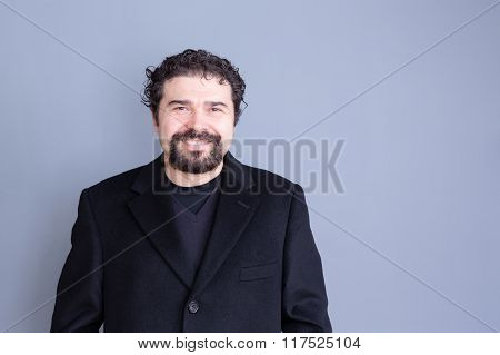 Smiling Man In Black Jacket Over Gray Background