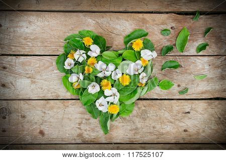 Heart Shape Arrangement Made Of Leaves And Flowers On Table