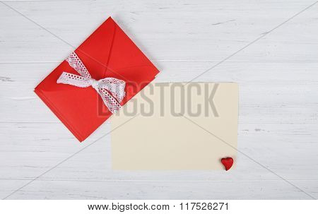 Red envelope and blank paper sheet on white wooden background