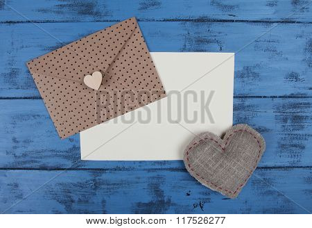 Envelope, heart and blank paper sheet on blue wooden background