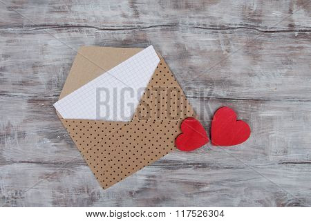 Valentine Day background with envelope and hearts on wood