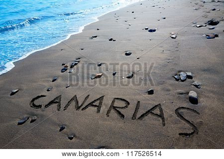 Canarias word written spell in black sand beach Canary Islands of Spain