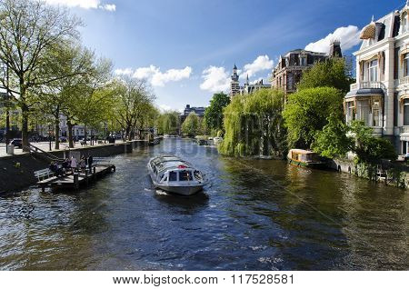 Tourist Boat Sailing In The Canals Of Amsterdam Holland