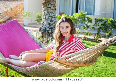 Happy Relaxed Young Woman Lying On Hammock In Casual Summer Dress