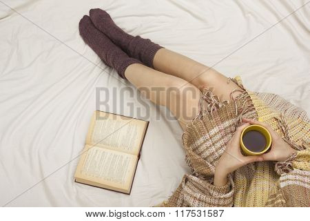 Woman on the bed with old book and cup of coffee in hands, top view point. Copy space for text. Soft