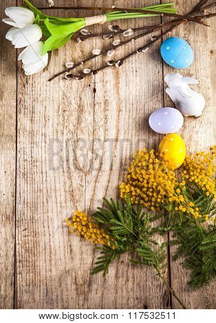 Easter still life with copyspace and spring flowers on wooden board