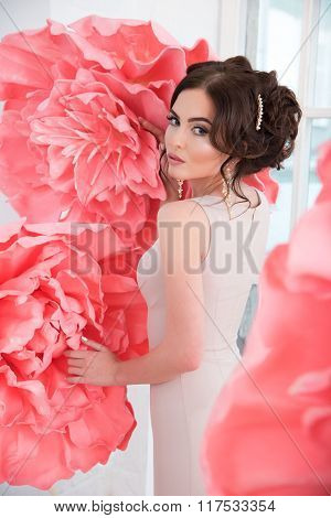 Beautiful Sexy Girl In A Long Dress With A Huge Pink Flowers Sitting By The Window