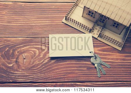 Real Estate Concept. Model house, keys, blank business card on wooden table. Top view. Toned image